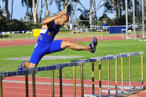Leon Baham leaps over a hurdle