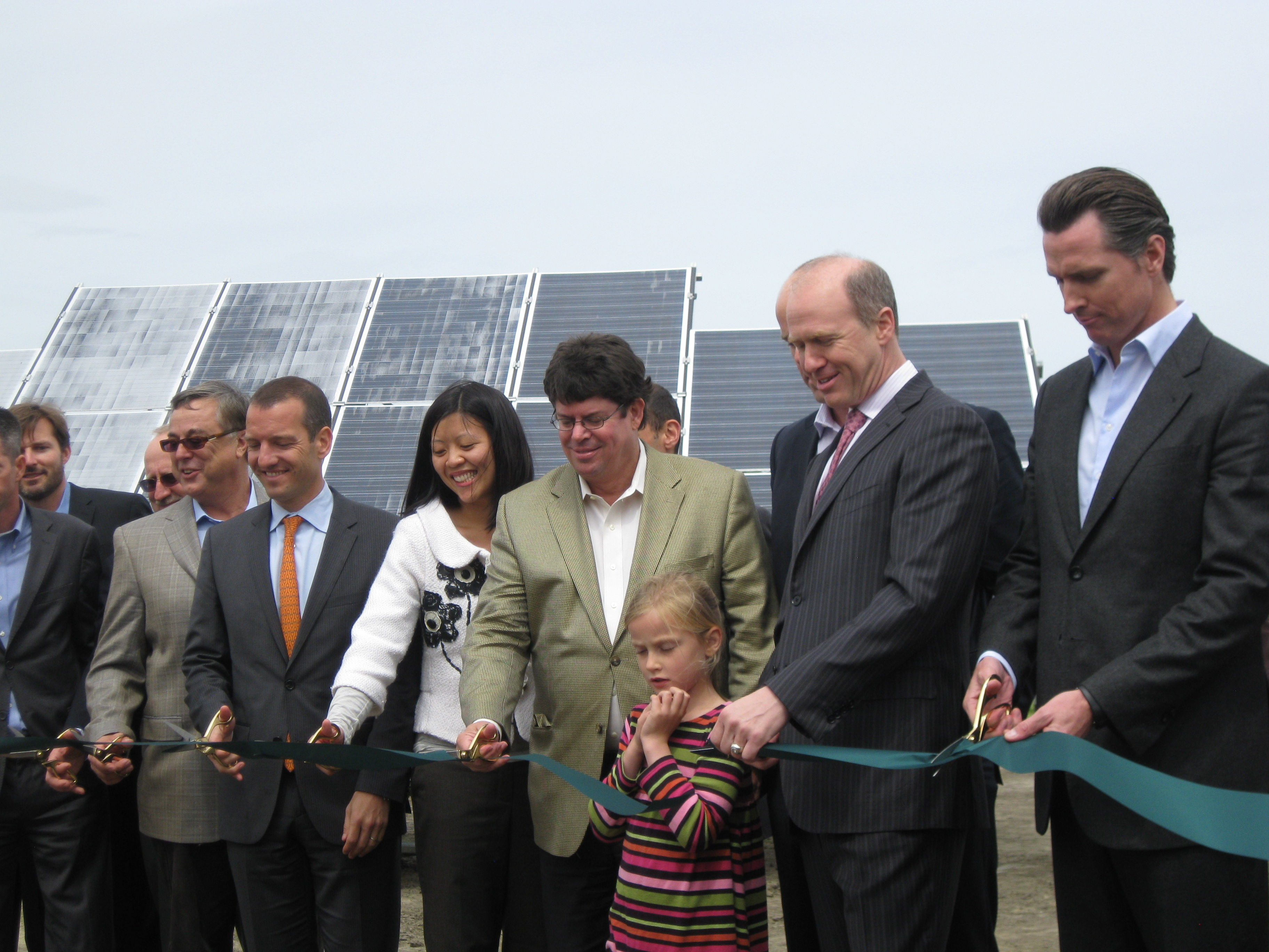 Ribbon cutting in front of the solar array