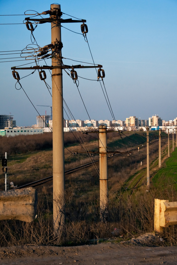 Power line poles  along the railway at city outskirts