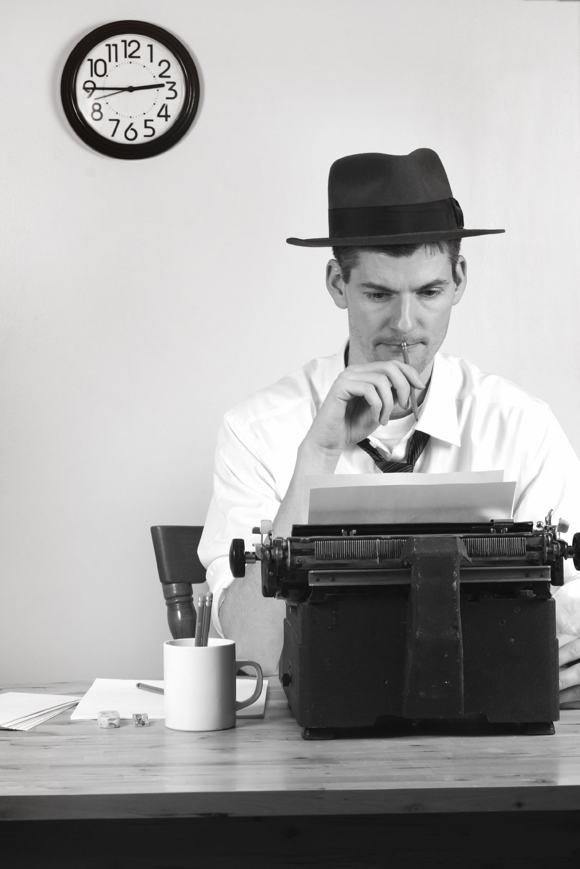 News reporter or journalist at a typewriter with clock on wall