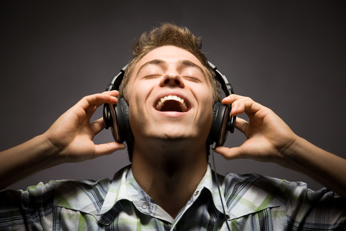 happy-man-listening-to-music-headphones-whilst-looking-up-under-shining-lig-o
