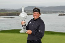 Phil Mickelson celebrates with the tournament trophy after winning at Pebble Beach earlier this year.