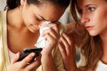 crying woman with mobile phone, courtesy of Shutterstock/Yuri Arcurs