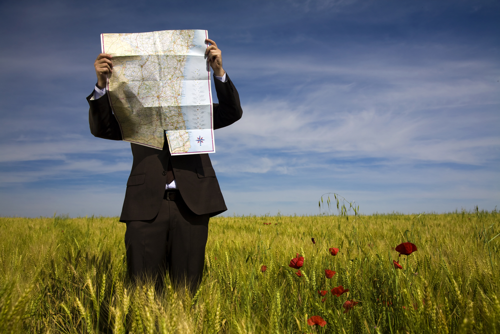 Business man with map lost field directions