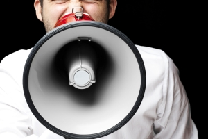Man with megaphone; shouting into megaphone