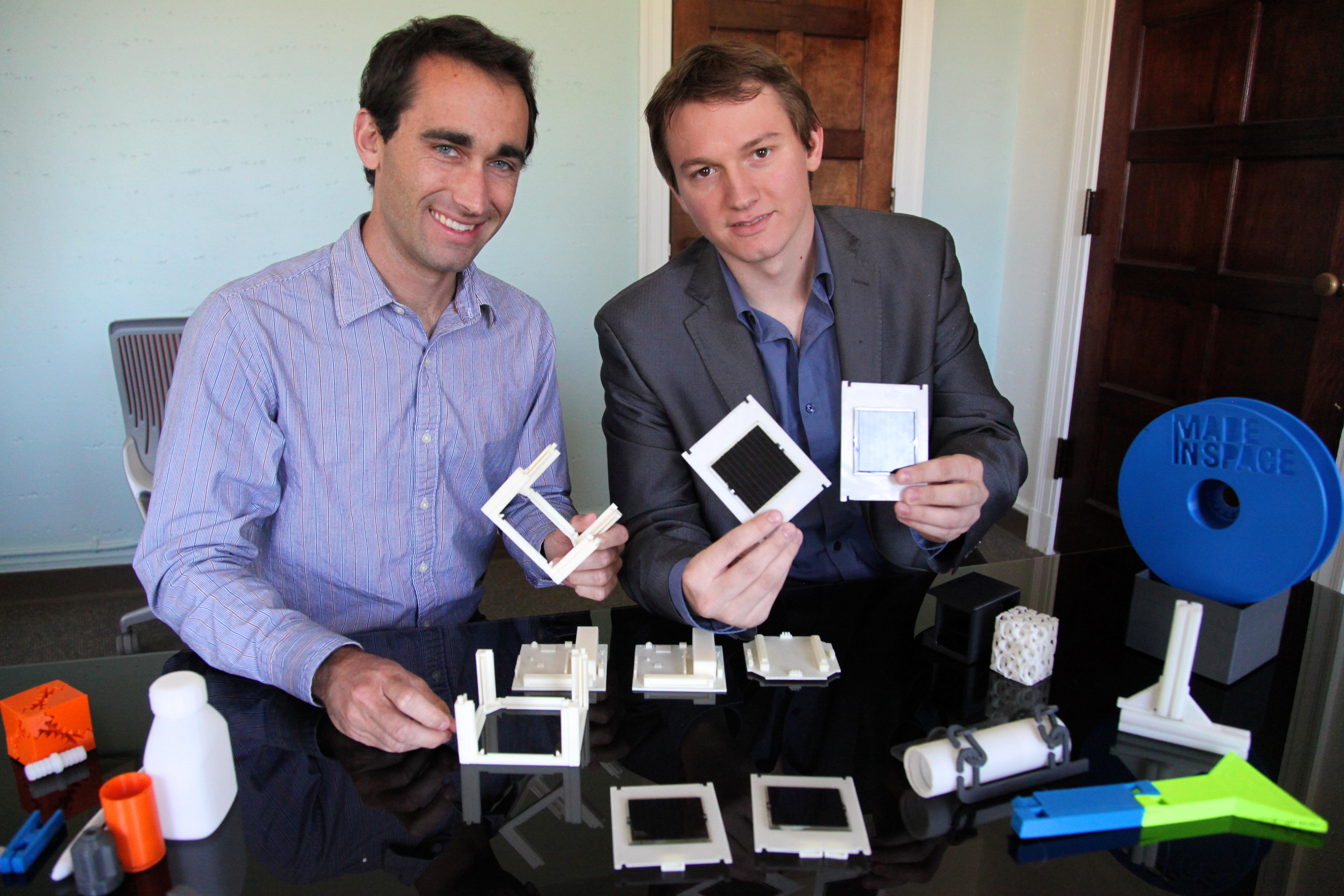 CTO Jason Dunn and CEO Aaron Kemmer show off a 3D printed CubeSat, plus other parts that could be made aboard the ISS. Photo by Signe Brewster.