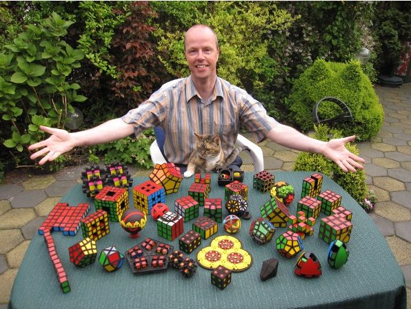Oskar van Deventer poses with his array of puzzles 3D printed via Shapeways.