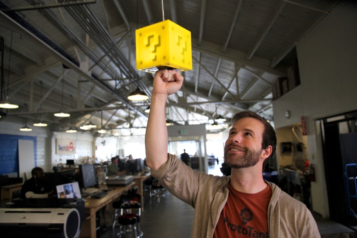 8-Bit Lit cofounder Adam Leavenworth punches a Question Block Lamp to light it up on TechShop's third floor. Photo by Signe Brewster