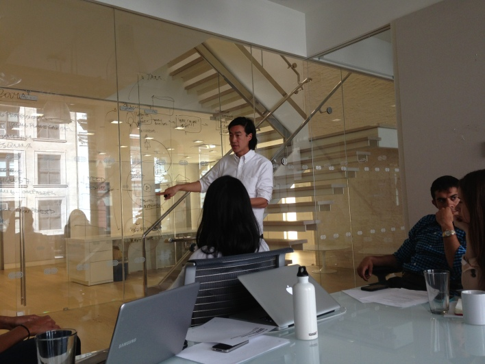 Advisor Albert Lee (standing) from IDEO speaks at NEA Studio.