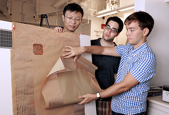 Princeton electrical engineering graduate students (from left) Liechao Huang, Josue Sanz Robinson and Warren Rieutort-Louis with a radio built into a thin sheet of plastic. Photo by Frank Wojciechowski