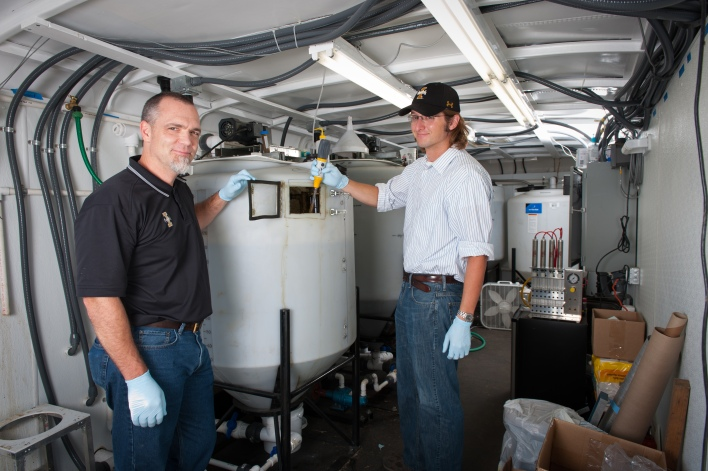 Civil engineering professor Erik Coats and PhD student Nick Guho work with a scale model of a tank that converts manure into biodegradable plastic. The tank can produce two to five pounds of plastic a day. Photo courtesy of University of Idaho