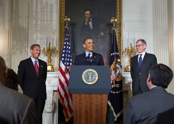 Tom Wheeler, pictured standing to the right of the president.