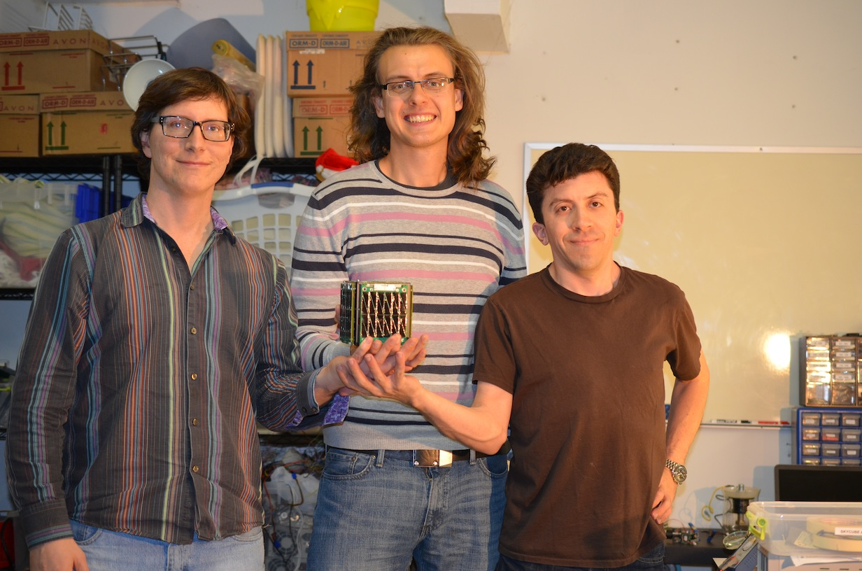 Tim DeBenedictis, Rouslan Dimitrov and Scott Cutler of Southern Stars holding the fully-integrated satellite for the first time. Photo courtesy of Southern Stars.