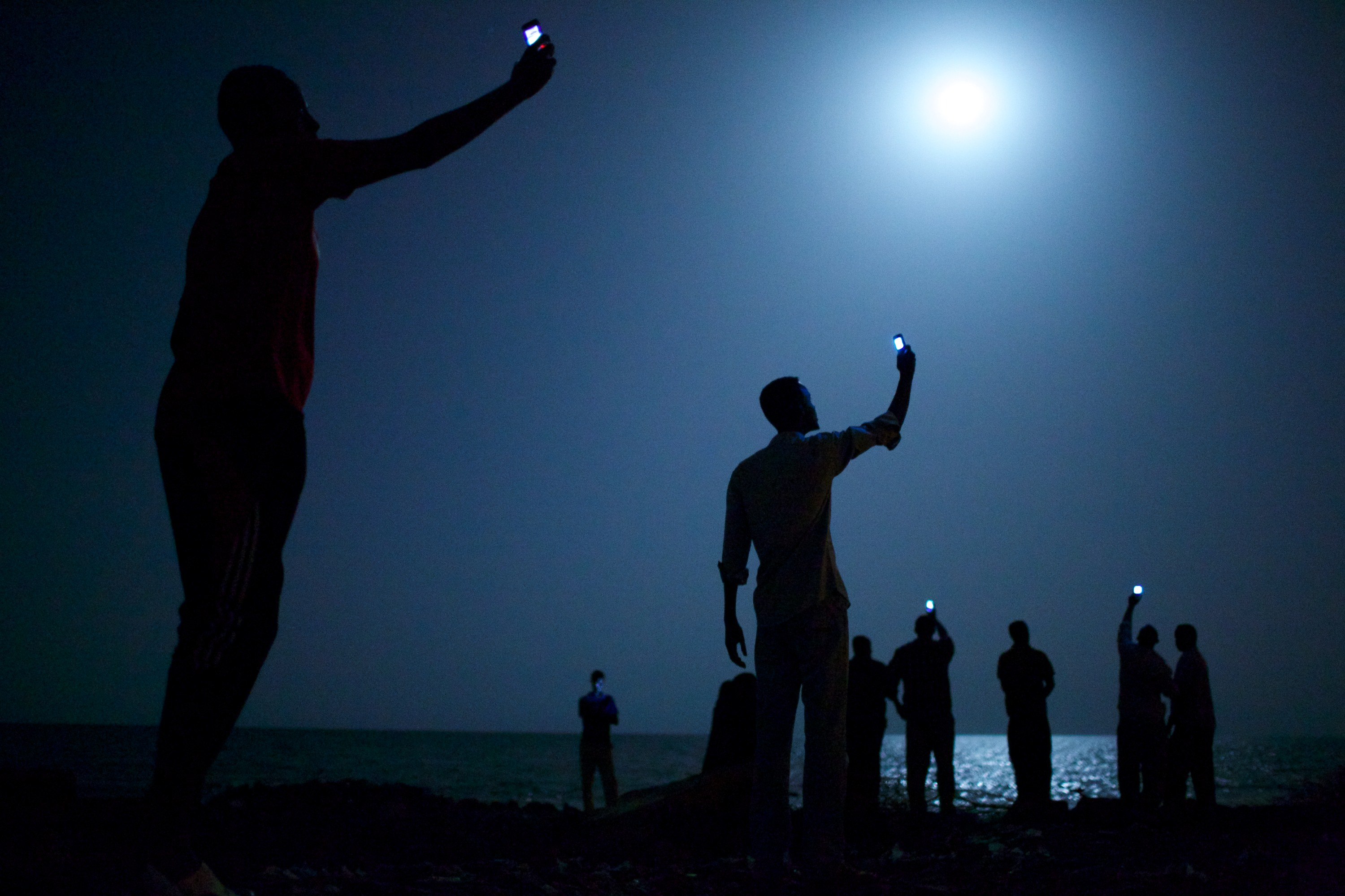 26 February 2013, Djibouti City, Djibouti -- African migrants on the shore of Djibouti city at night, raising their phones in an attempt to capture an inexpensive signal from neighboring Somalia—a tenuous link to relatives abroad. Djibouti is a common stop-off point for migrants in transit from such countries as Somalia, Ethiopia and Eritrea, seeking a better life in Europe and the Middle East. Photo: John Stanmeyer, USA, VII for National Geographic