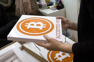 HONG KONG - FEBRUARY 28: A worker holds a sign at the first bitcoin retail store open in Hong Kong on February 28, 2014 in Hong Kong. Asia Nexgen, a Hong Kong based bitcoin exchange has launched a physical store enabling customers to purchase bitcoin and store it in their digital bitcoin wallets. Bitcoin Group HK and Hong Kong Bitcoin ATM plan to launch bitcoin 'ATM's machines in the area. in 2008 Bitcoin was launched as an alternative currency, with the commodity boasting the ability to be transferred without the need of the traditional monetary banking system. (Photo by Lam Yik Fei/Getty Images)