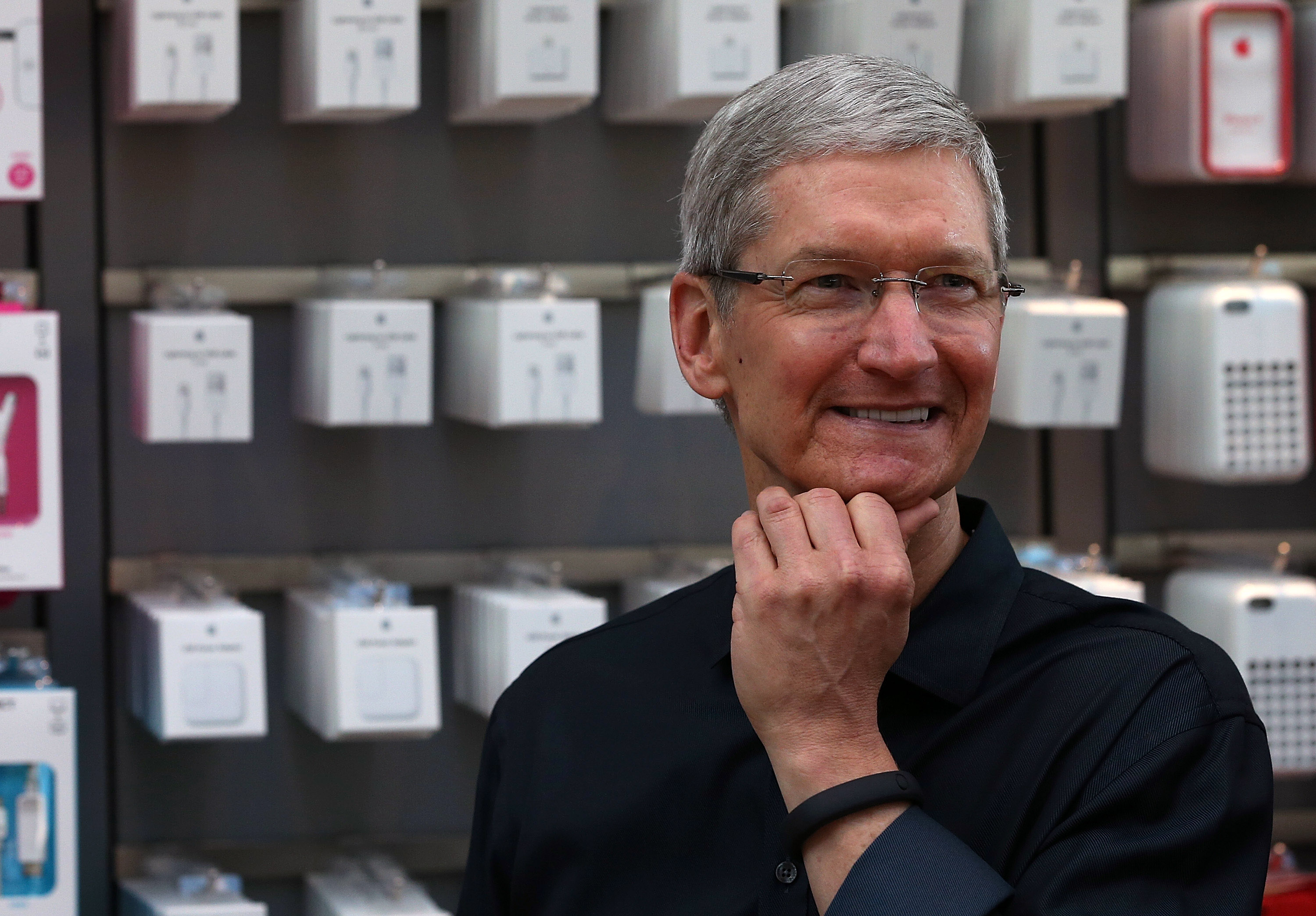 Apple CEO Tim Cook looks on, wearing a Nike Fuelband, before the Apple Store opens to sell the new iPhone on September 20, 2013 in Palo Alto, California. Photo by Justin Sullivan/Getty Images