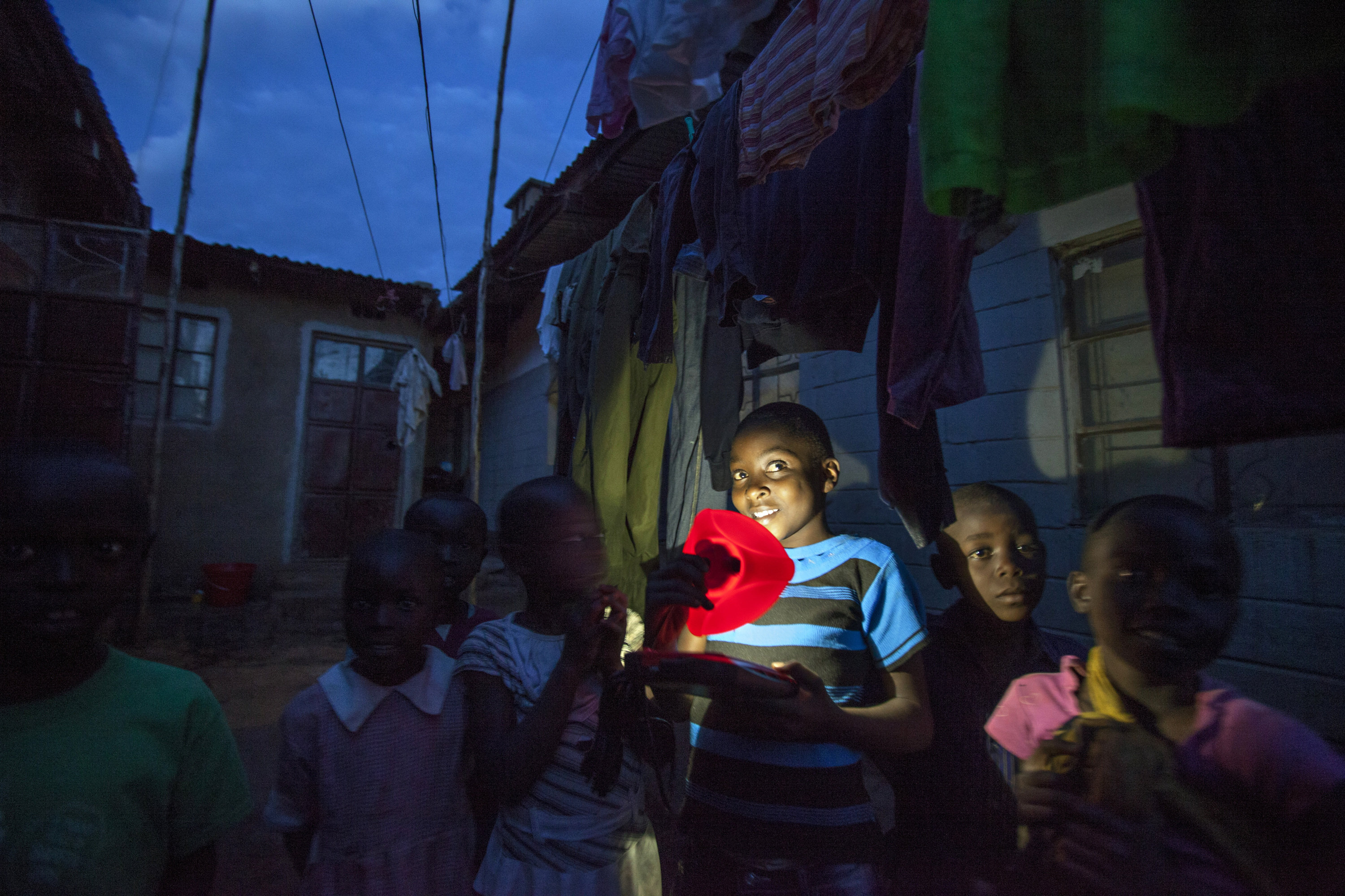A child in Kenya holds a light powered by a solar panel sold by M-KOPA.