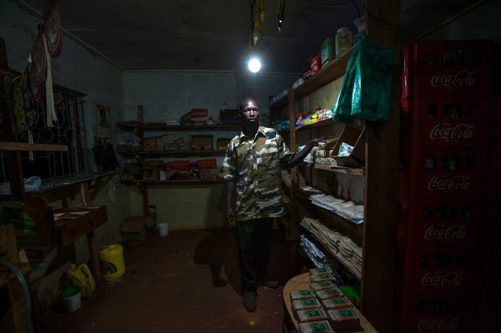 A shop owner lights up his shop with a solar system sold by M-KOPA