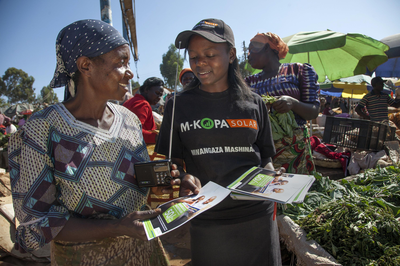 A M-KOPA retailer hands out flyers about the solar product. Courtesy of M-KOPA, Georgina Goodwin.