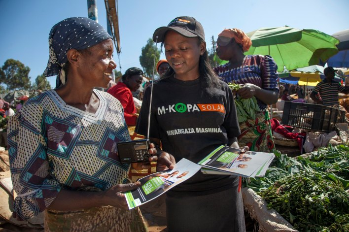 A M-KOPA retailer hands out flyers about the solar product. Courtesy of M-KOPA, Georgina Goodwin.