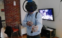 Qualcomm Ventures investment manager Gareth Keane fights off zombies during a demo of Survios' virtual reality gaming system. A bulb attached to the top of the Oculus Rift headset senses the location of the player's feet and hands, while two Sixense controllers allow players to shoot and pick up items.