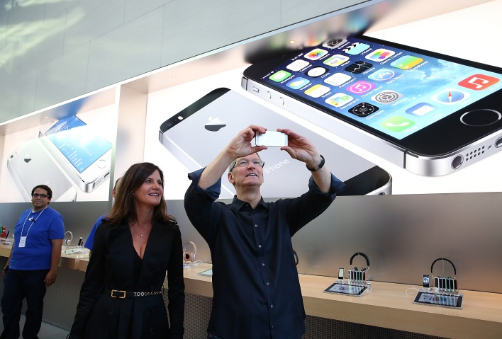 Katie Cotton, Apple vice president of corporate communications (L) looks on as Apple CEO Tim Cook (R) uses an iPhone to take a picture of customers waiting in front of an Apple store to purchase the new iPhones on September 20, 2013 in Palo Alto, California. (Photo by Justin Sullivan/Getty Images)