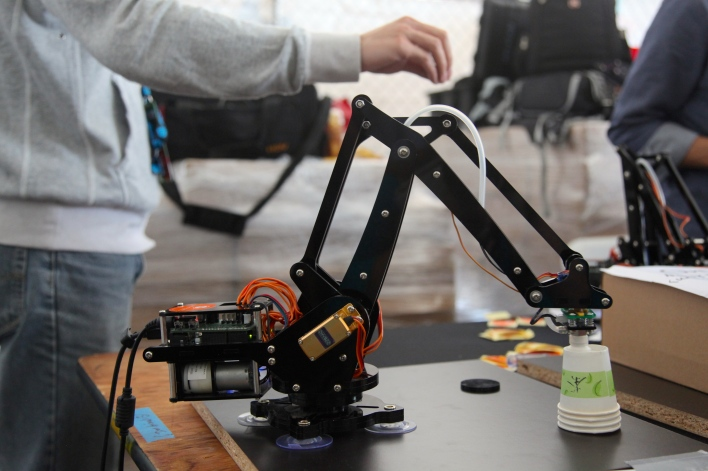 A uArm robotic arm mimics a human's hand motions picked up by a Leap Motion controller to pick up and move paper cups. Photo by Signe Brewster.