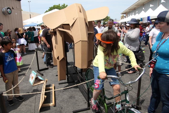 A girl pedals to move the legs of a cardboard elephant. Photo by Signe Brewster.