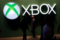 Game enthusiasts walk past the Microsoft Xbox logo at the Eurogamer Expo 2013 at Earl's Court exhibition centre in London on September 26, 2013.  Leon Neal/AFP