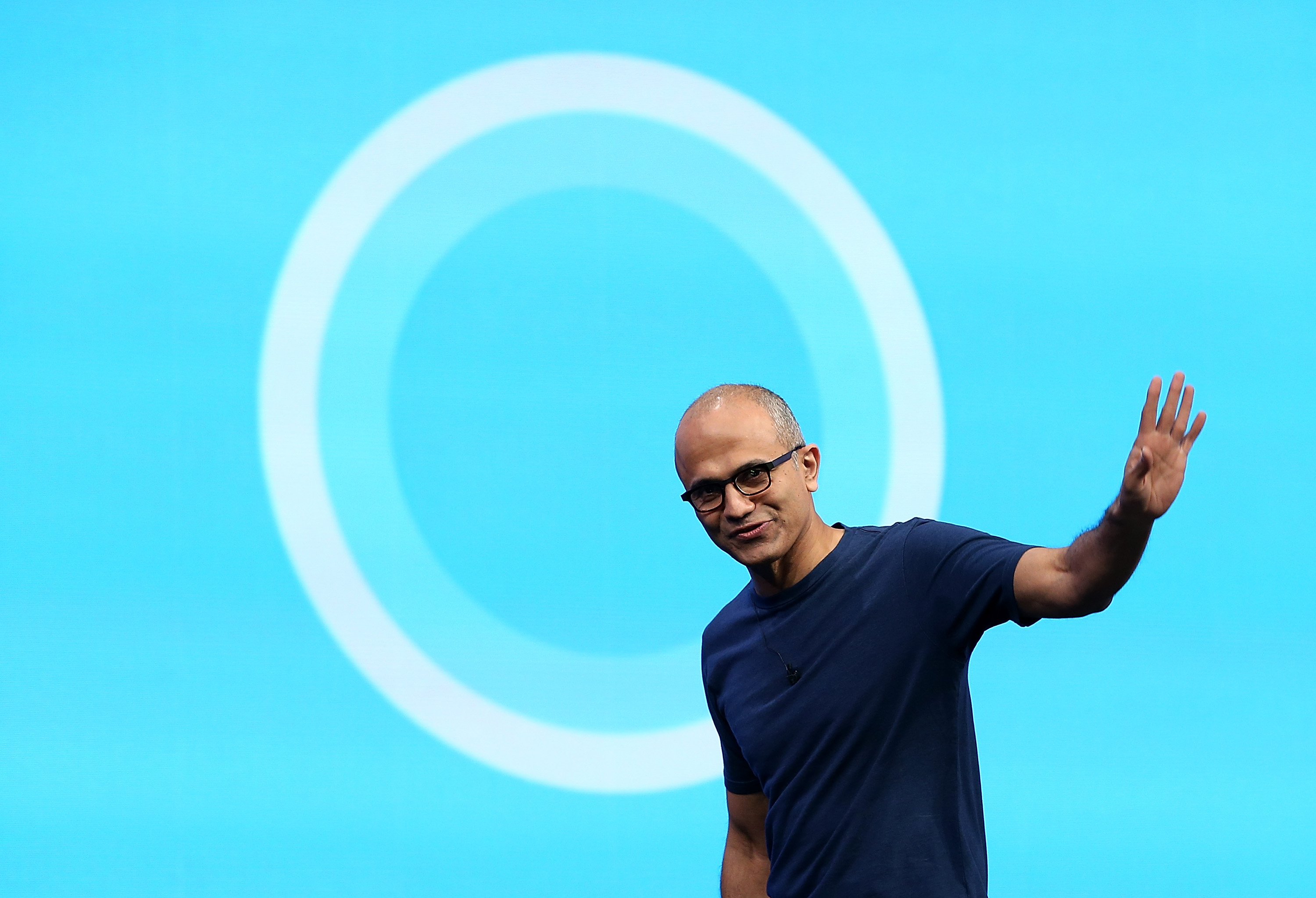 Microsoft CEO Satya Nadella walks in front of the new Cortana logo as he delivers a keynote address during the 2014 Microsoft Build developer conference on April 2, 2014 in San Francisco, California.