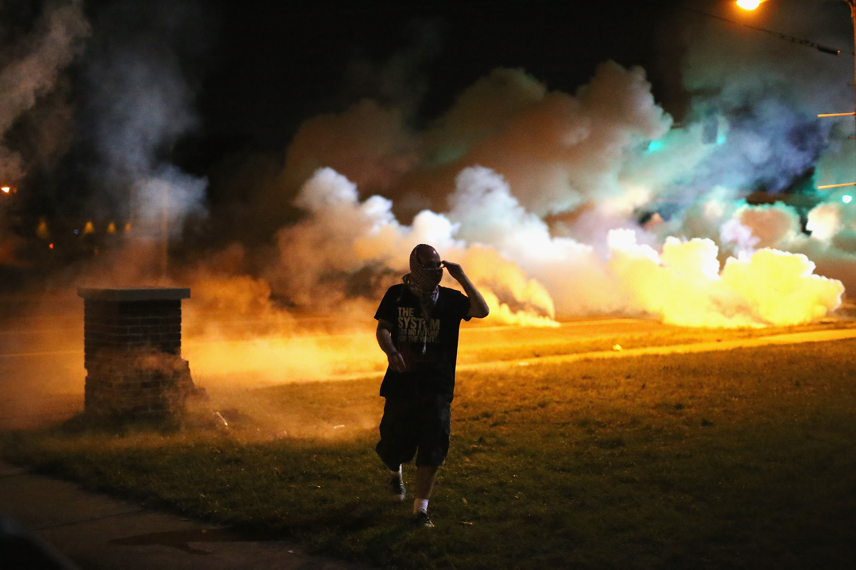 Demonstrators, protesting the shooting death of teenager Michael Brown, flee as police shoot tear gas into the crowd of several hundred after someone reportedly threw a bottle at the line of police on August 13, 2014 in Ferguson, Missouri.  (Photo by Scott Olson/Getty Images)