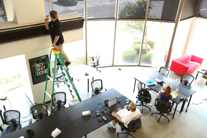 The Reno Collective co-working space in Startup Row in Reno, Nevada. An member tests the wireless mesh network to get it ready for a hardware meetup later that night. Image courtesy of Katie Fehrenbacher, Gigaom.