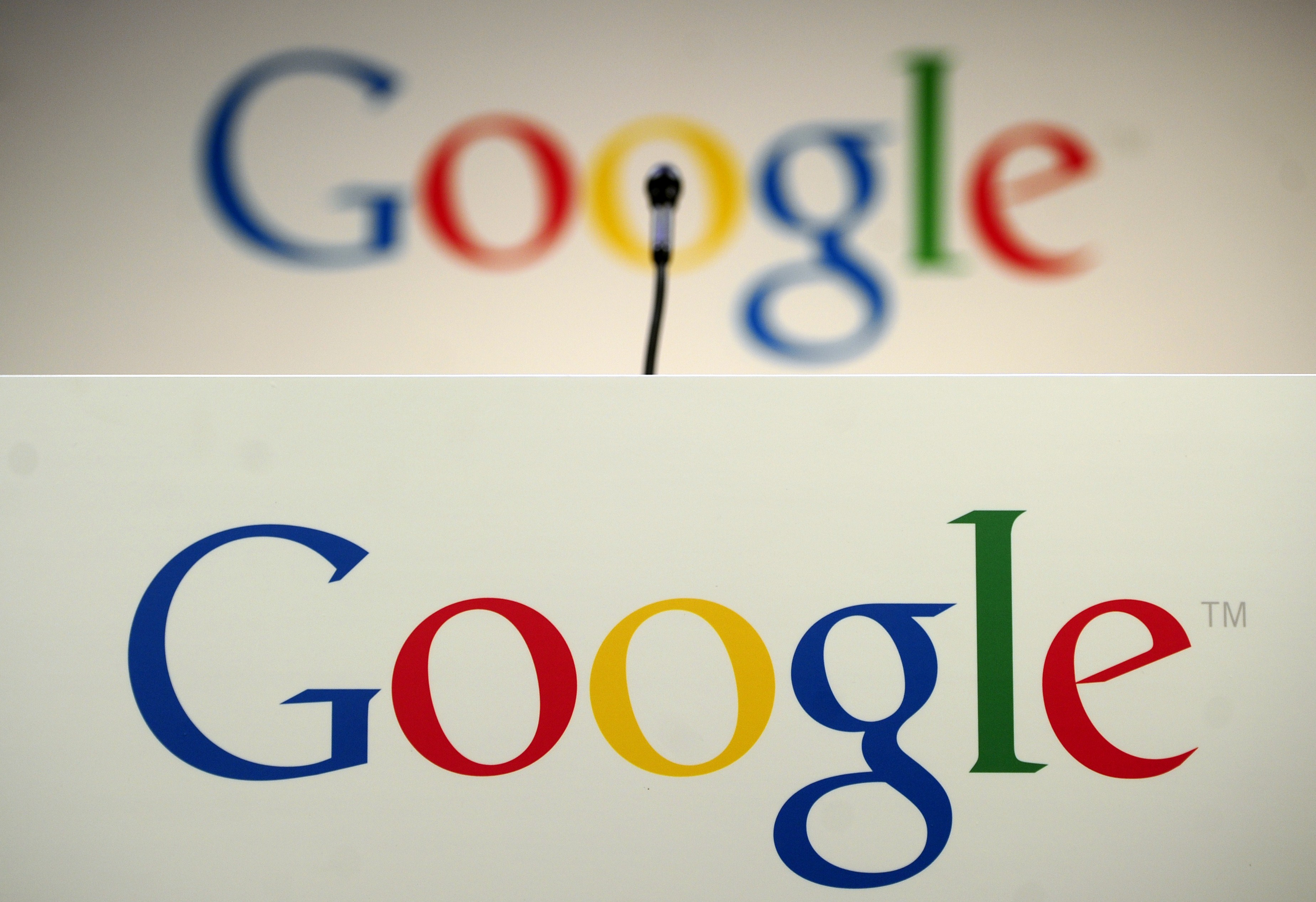 A microphone stands in front of a Google logo during a press annoucement at Google headquarters in New York, May 21, 2012. (Photo by Emmanuel Dunand/AFP/Getty Images)