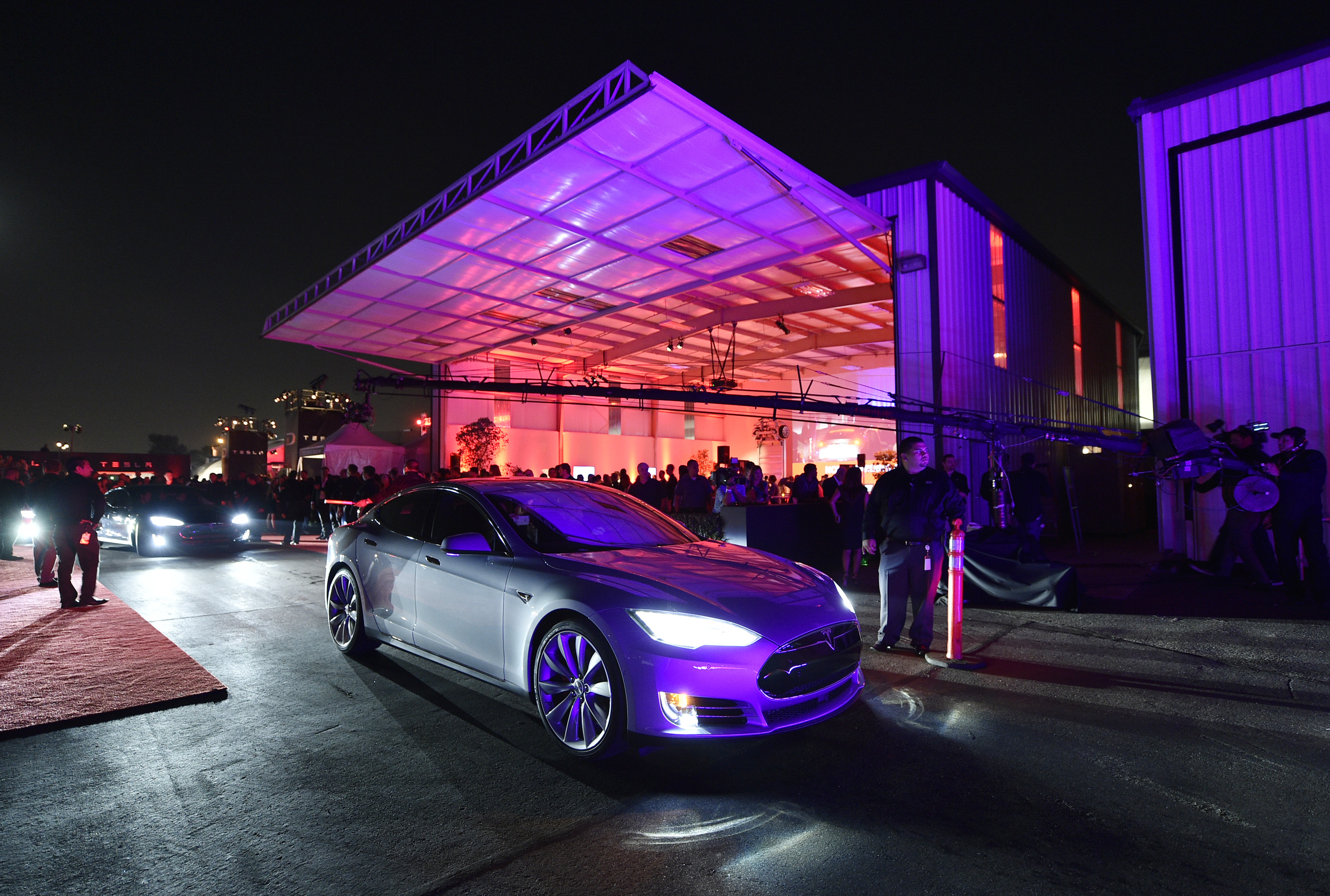 """Tesla owners take a ride in the new Tesla """"D"""" model electric sedan after Elon Musk, CEO of Tesla, unveiled the dual engine chassis of the new Tesla 'D' model, a faster and all-wheel-drive version of the Model S electric sedan, at the Hawthorne Airport October 09, 2014 in Hawthorne, California. (Photo by Kevork Djansezian/Getty Images)"""