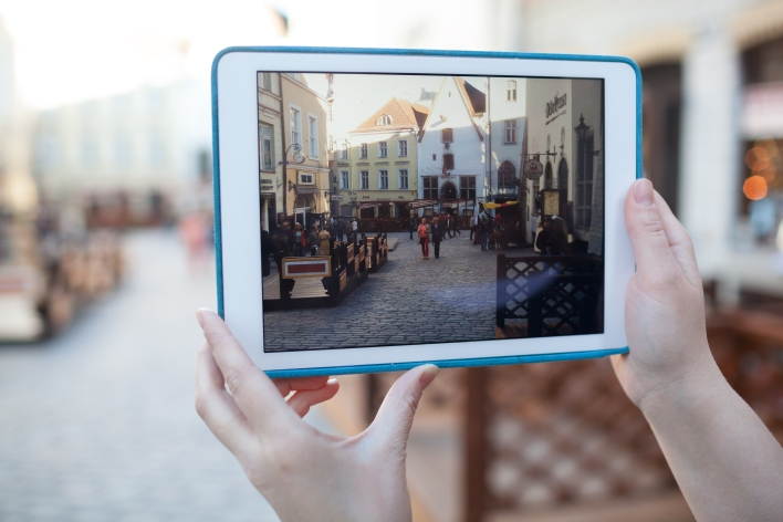 A woman records video on a tablet of the ancient streets of Tallin, Estonia. Photo by d13/Shutterstock.com