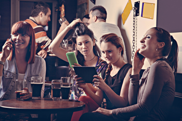 Young people in a bar with smartphones