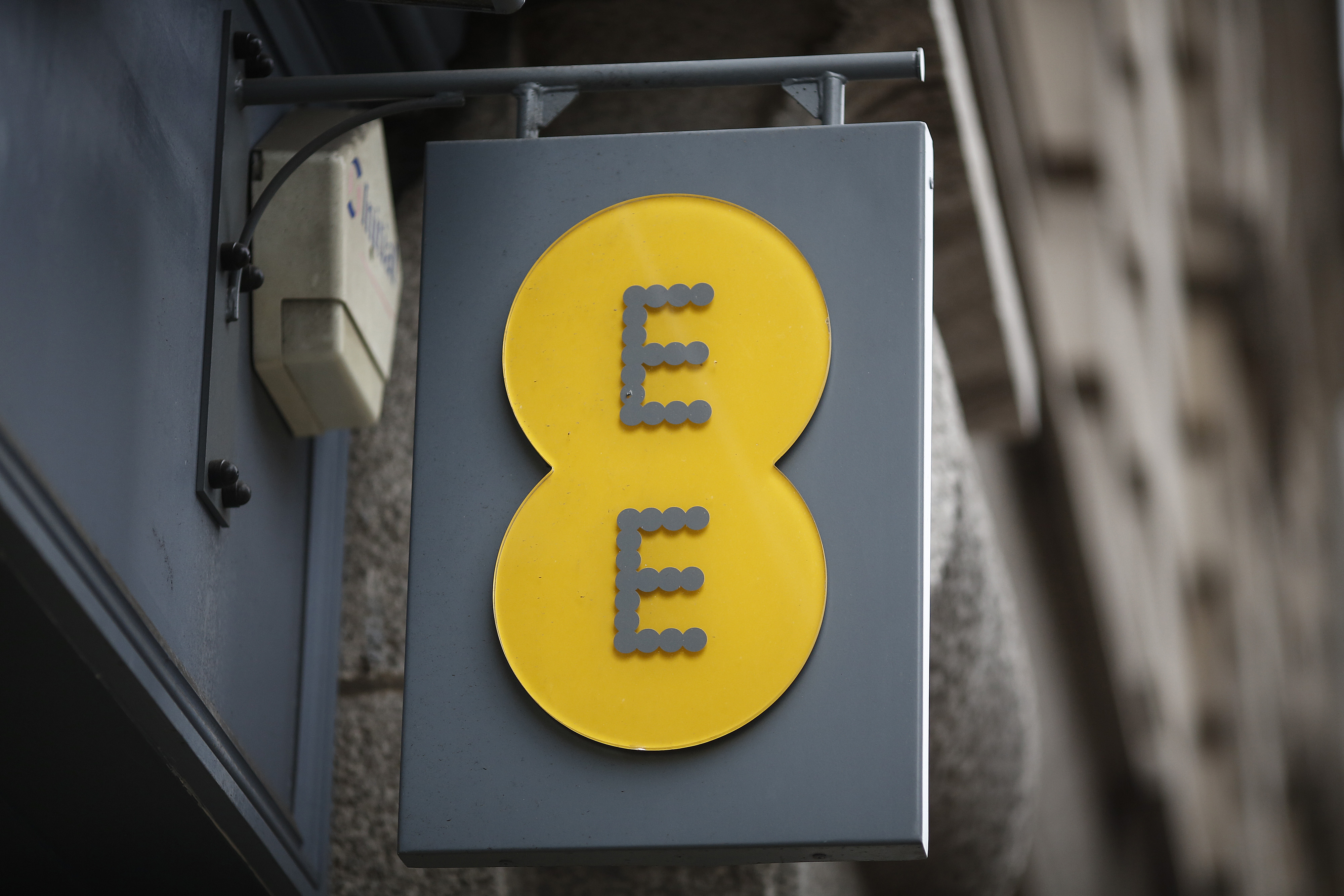 The company logo hangs on a sign outside an EE mobile phone store in London, U.K., on Tuesday, Dec. 24, 2013.