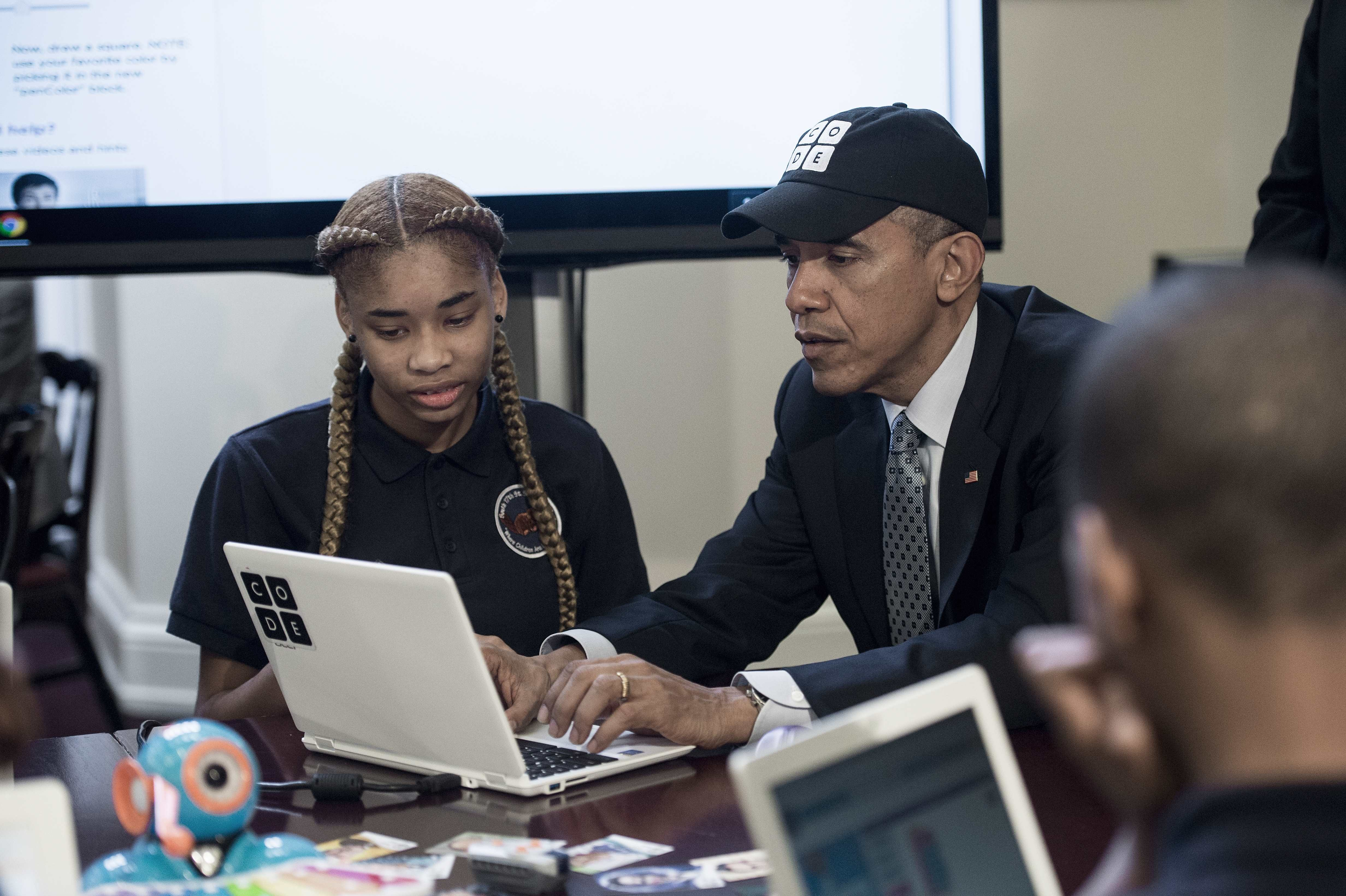 US President Barack Obama works with a middle-school student on December 8, 2014.