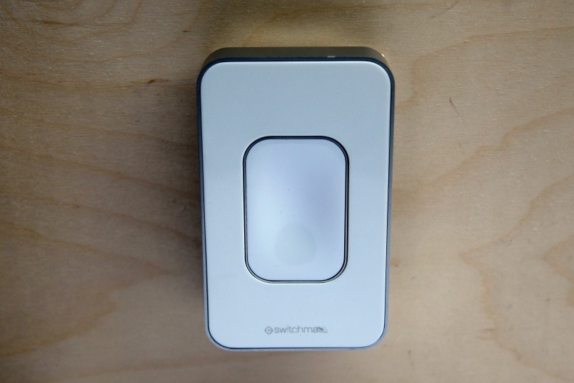 The Switchmate device sits on top of traditional light switches.