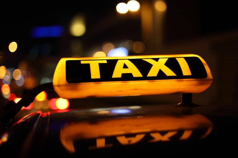Yellow taxi sign at night