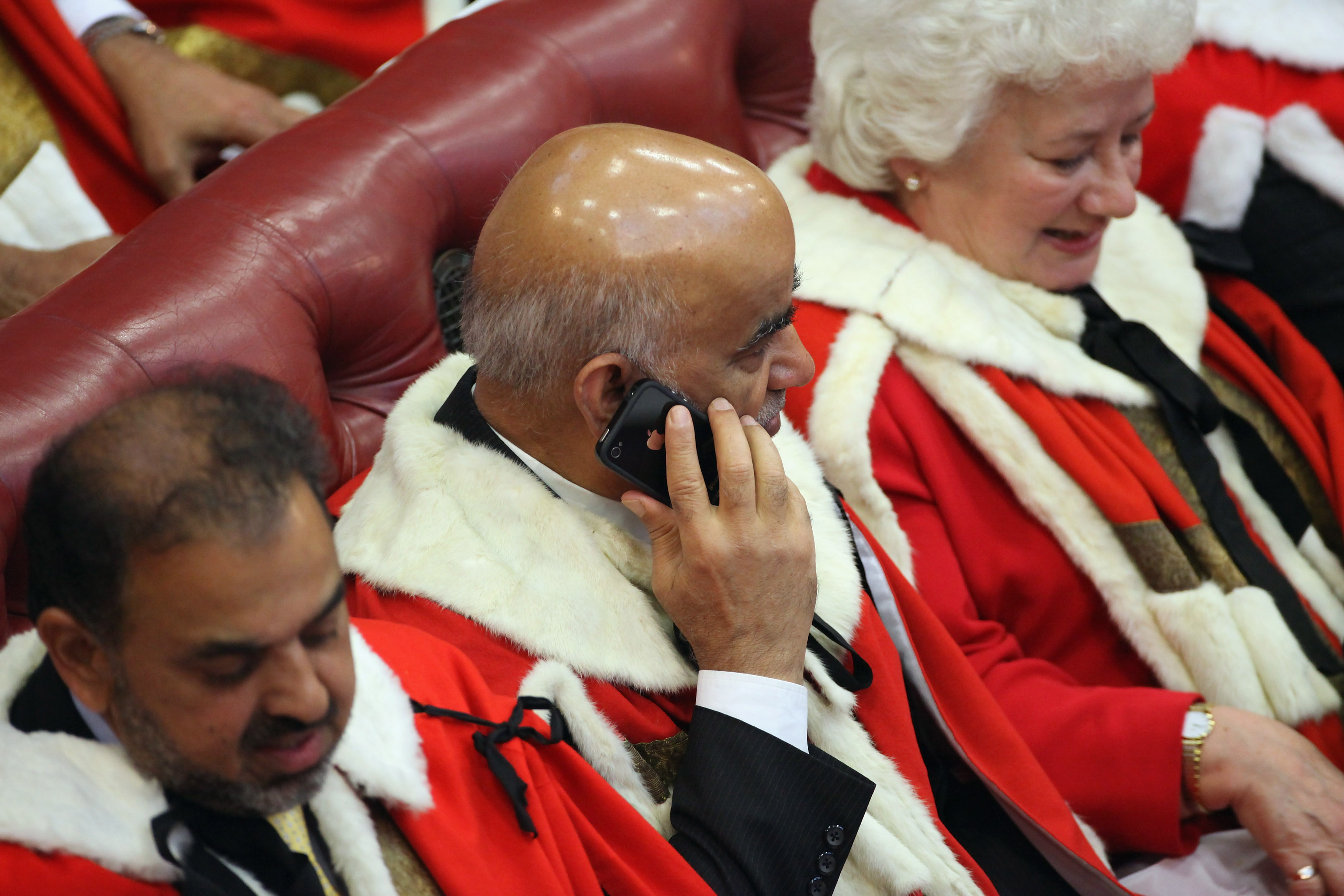 A peer uses a mobile smartphone in the Chamber of the House of Lords in London on May, 9, 2012.