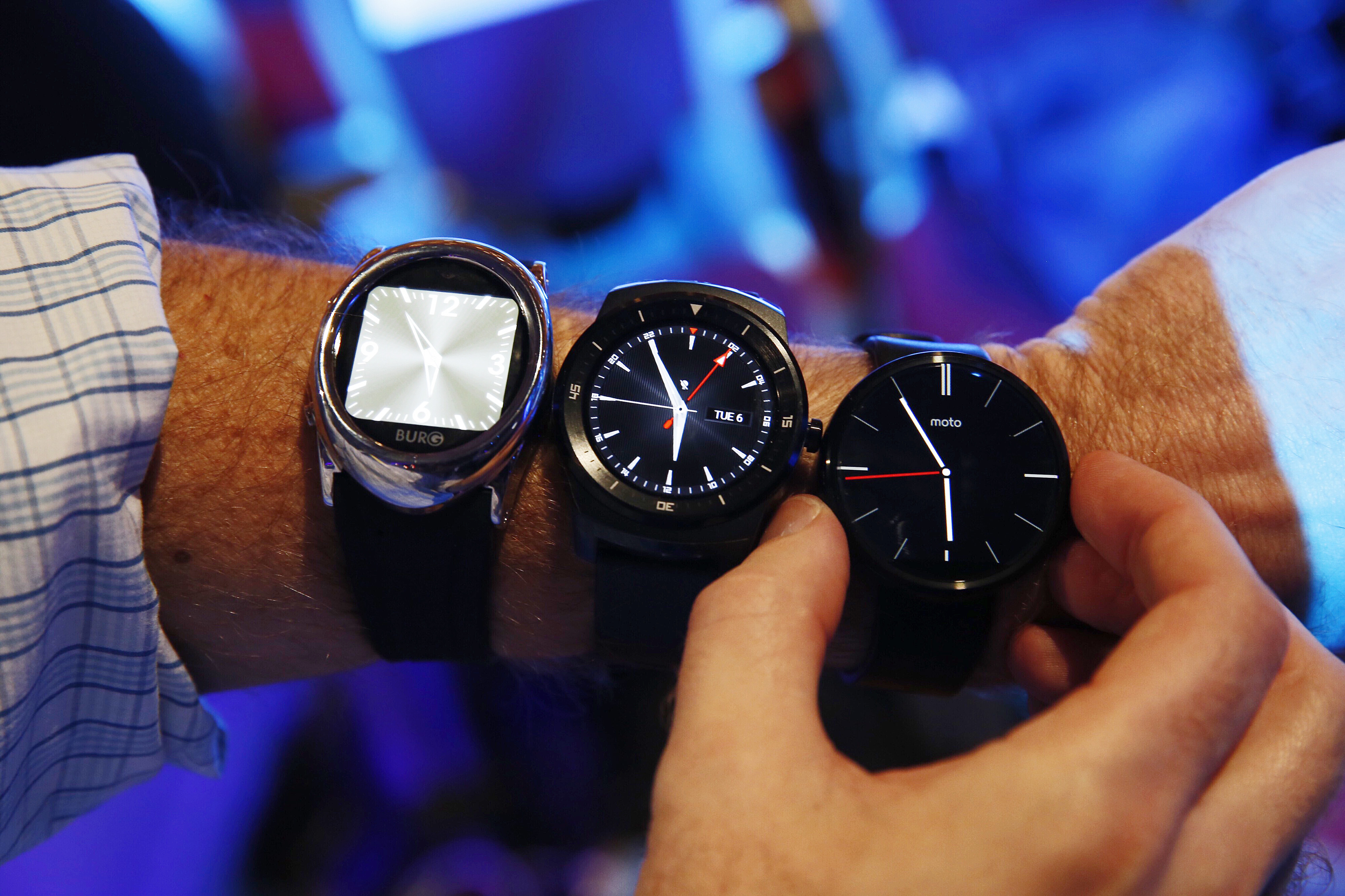 Smartwatches the Burg 12, left, the LG G Watch R, center, and the Moto 360 are arranged for a photograph during CES in Las Vegas on Jan. 6, 2015.