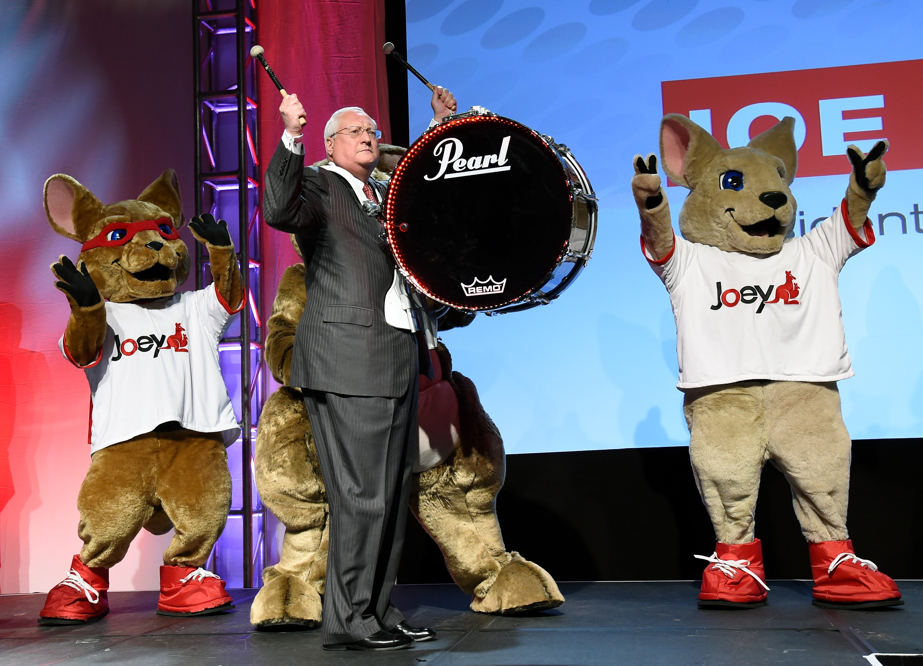 DISH President and CEO Joe Clayton makes his entrance playing a drum with kangaroo characters at a press event for DISH at the 2015 International CES on January 5, 2015 in Las Vegas, Nevada.