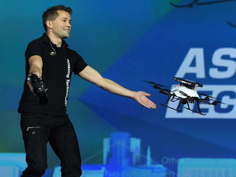 A worker demonstrates the collision avoidance capability of an AscTec Firefly multi-copter drone with Intel RealSense cameras at CES on January 6, 2015.