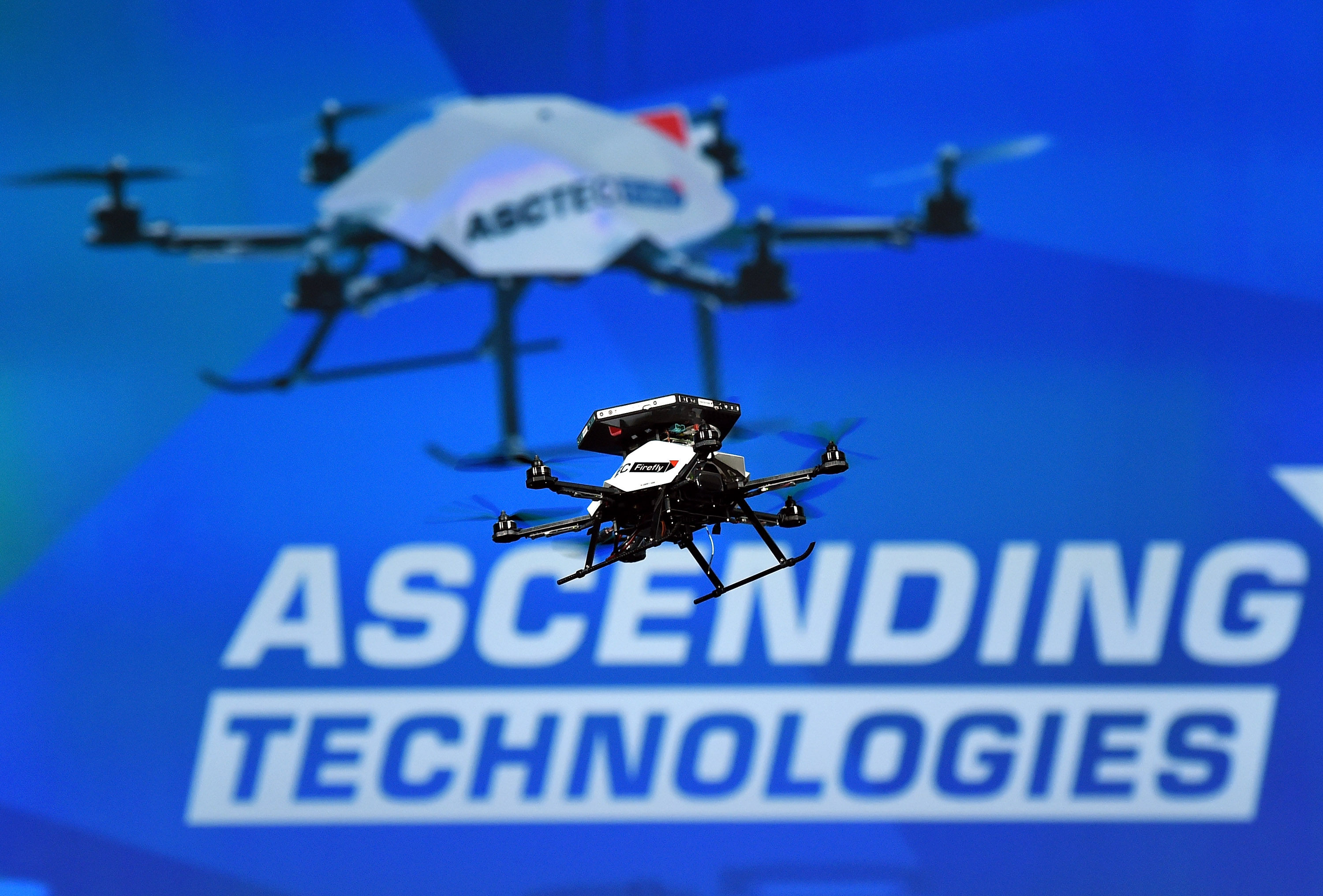 A worker demonstrates the AscTec Firefly multi-copter drone at CES on January 6, 2015.