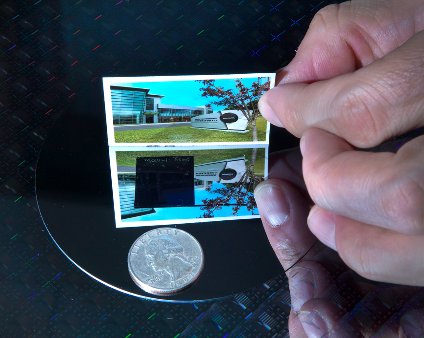 A closeup shows how the nanotextured square of silicon completely blocks reflection compared with the surrounding silicon wafer.