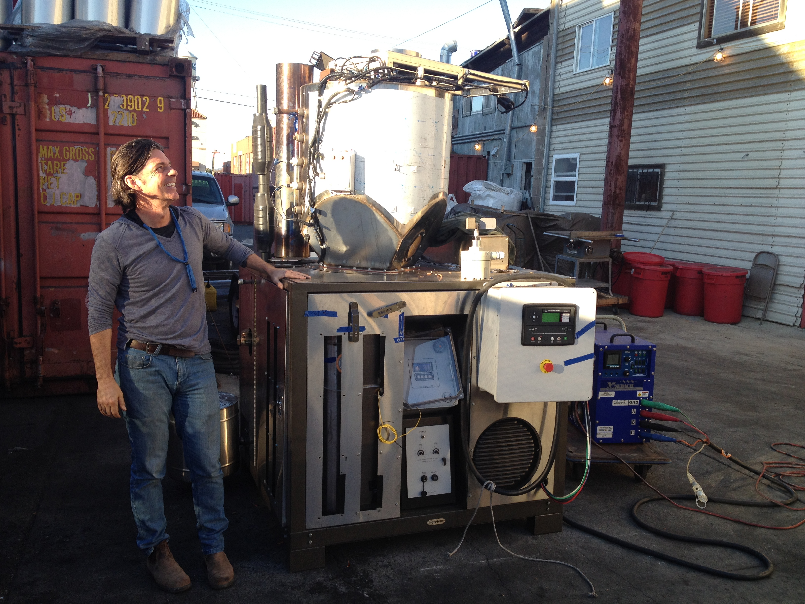 Tom Price, Director of Strategic Initiatives at All Power Labs, stands next to the Power Cube, a mobile gasifier.