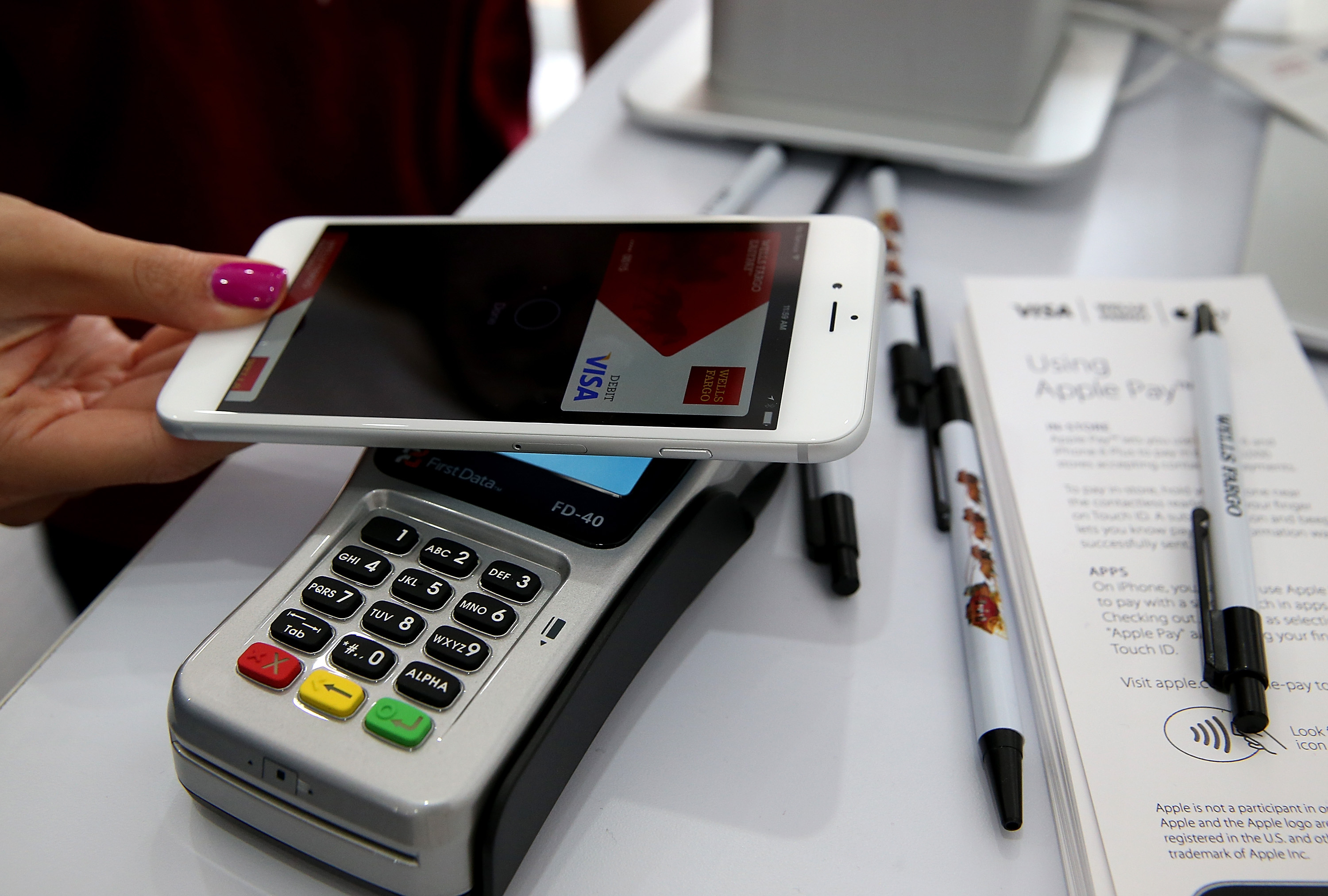 A worker demonstrates Apple Pay on October 20, 2014 in San Francisco.
