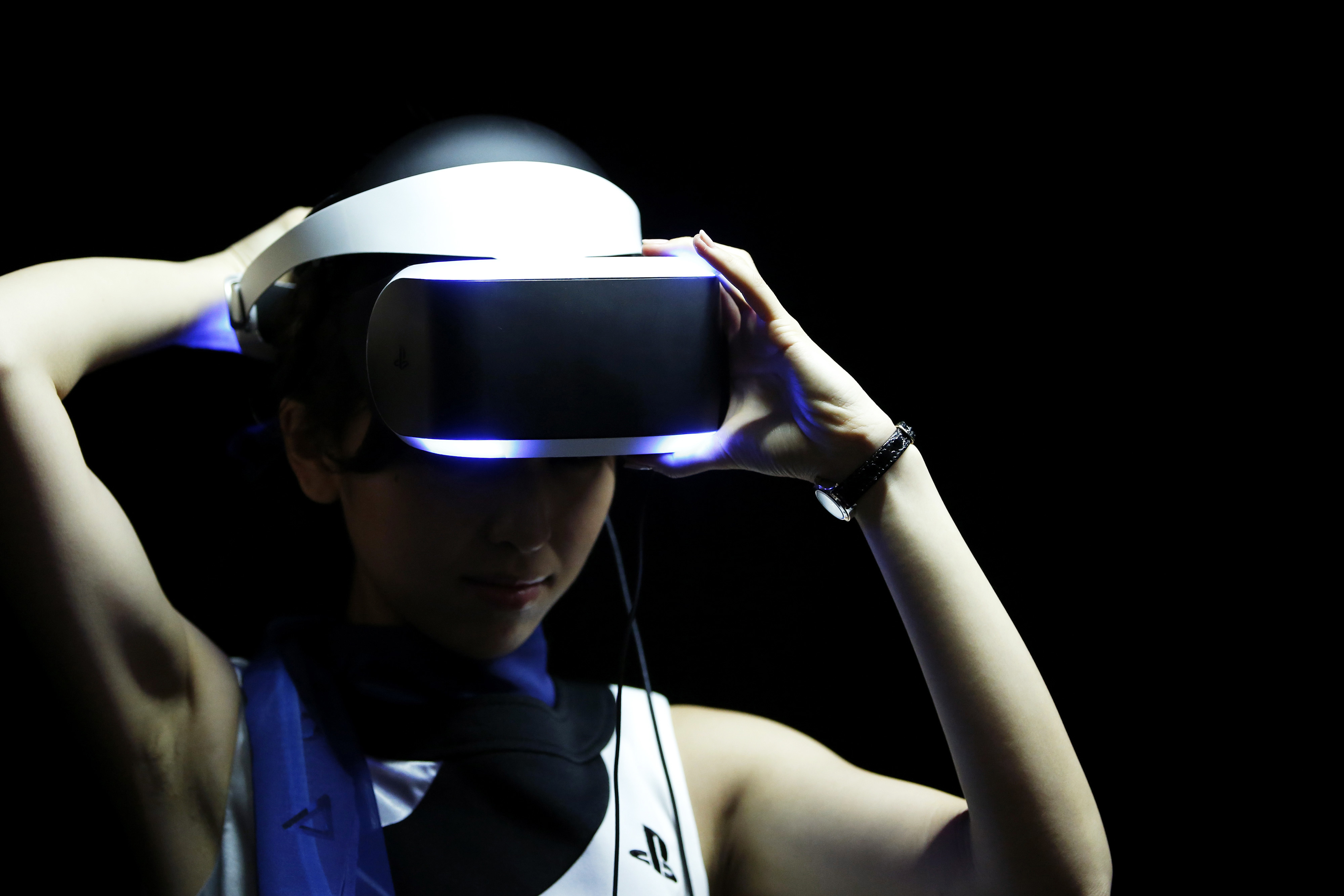 A booth attendant demonstrates the Sony Corp. Project Morpheus virtual reality headset for a photograph at the Tokyo Game Show 2014 in Chiba, Japan, on Thursday, Sept. 18, 2014.
