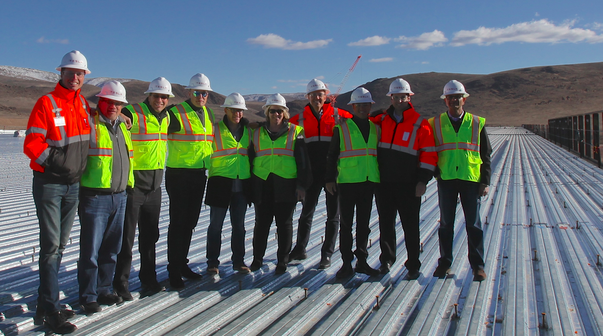 Tesla investors and execs standing on the roof of the battery factory.